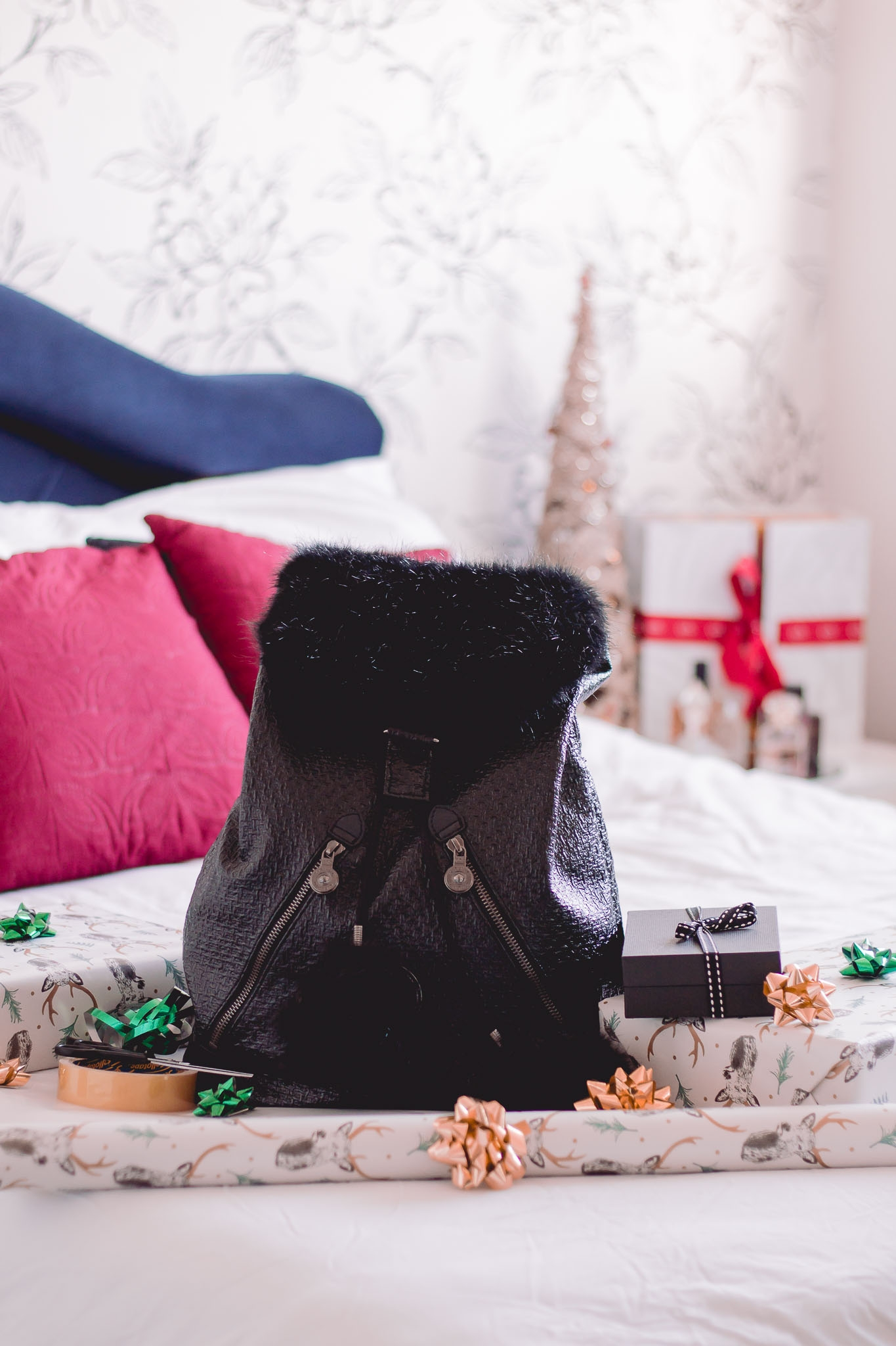 kipling bag on bed with gifts and gift wrapping