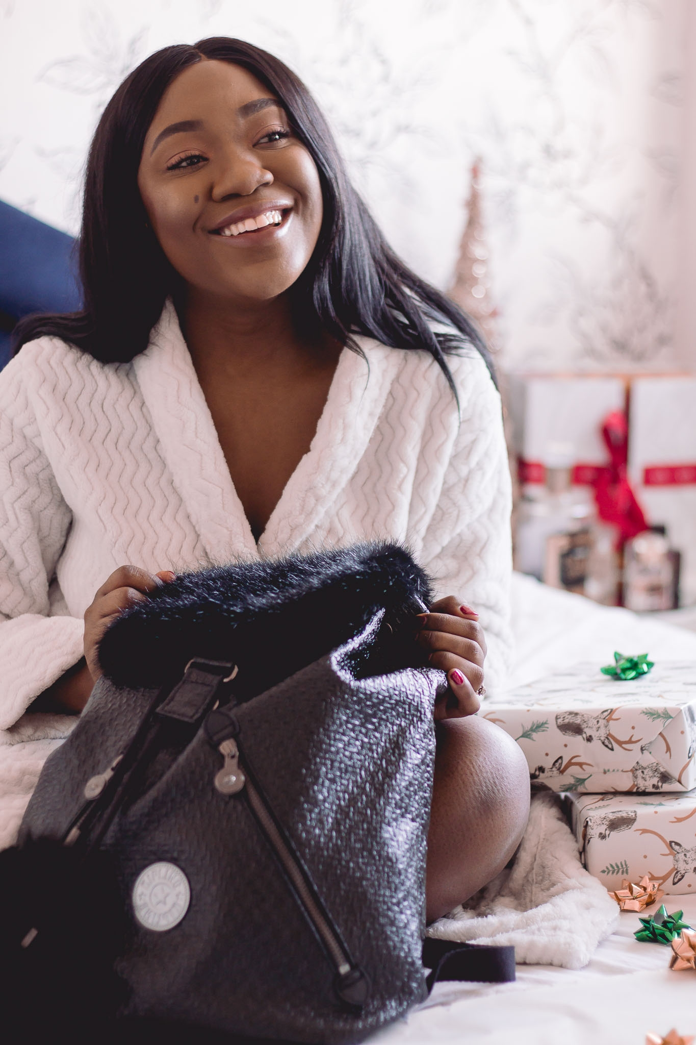 smiling girl sitting on bed with gift