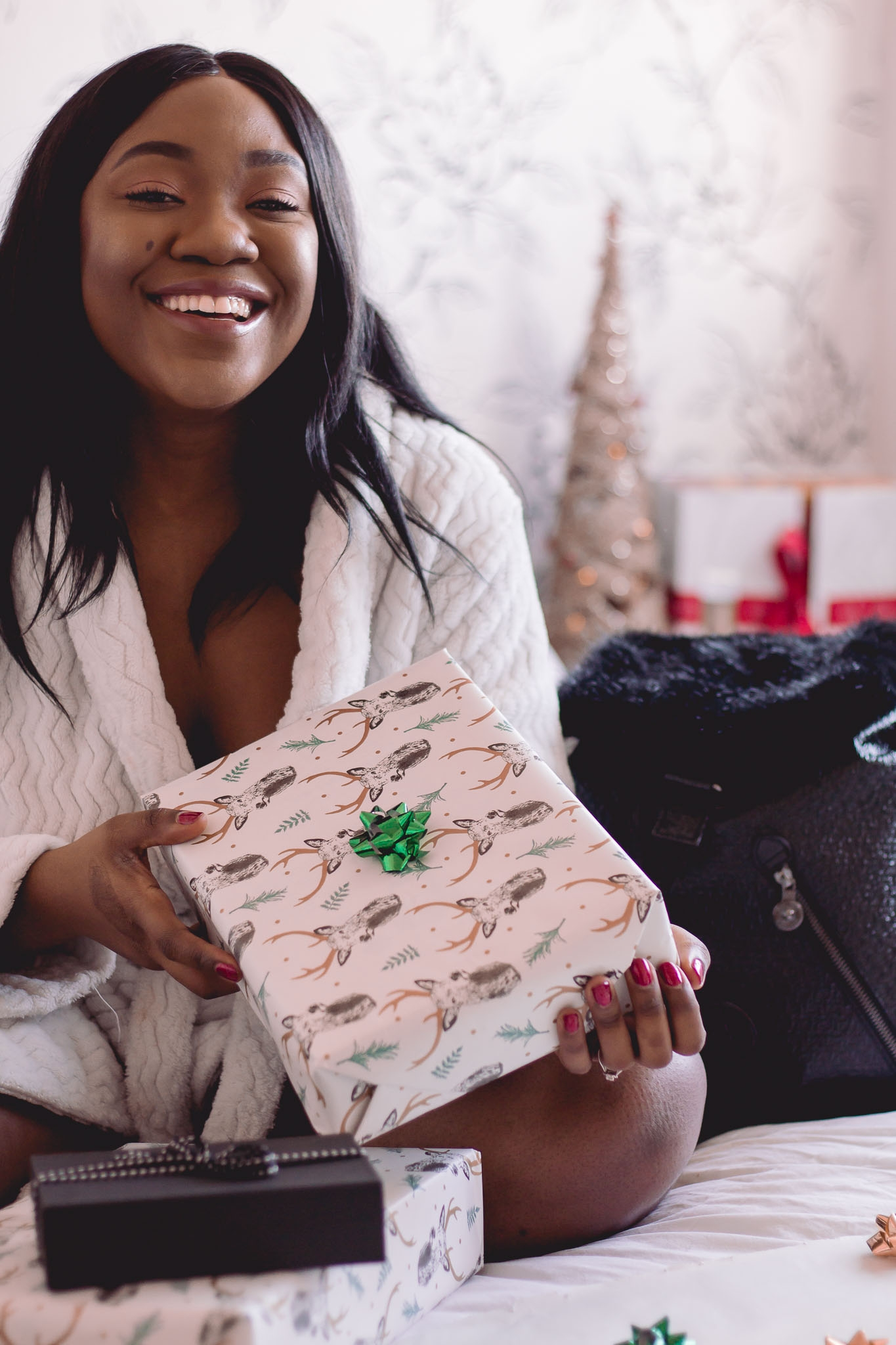girl on bed laughing and holding gift